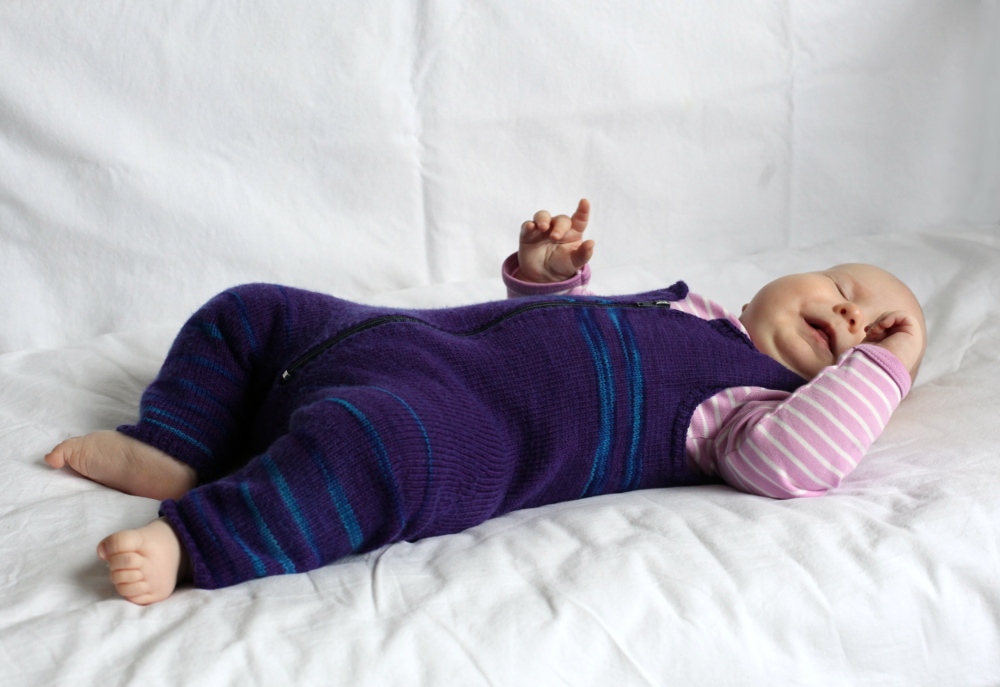 Baby wearing a purple. knitted overall