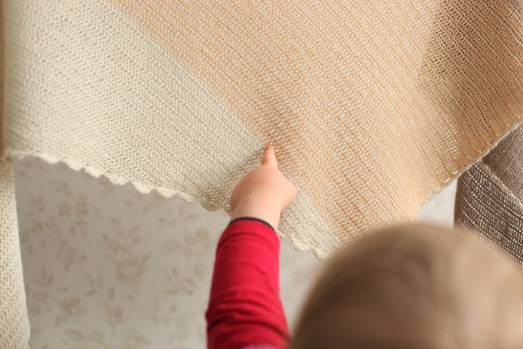 A toddler pointing at the crocheted shawl