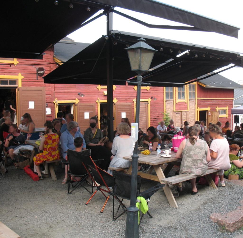 Ihmisiä istumassa, neulomassa ja juttelemassa Toivolan pihassa